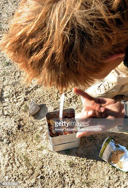Prince Harry licks his fingers as he eats a breakfast of biscuits mixed with jam and butter in the desert on February 19 2008 in Helmand Province...