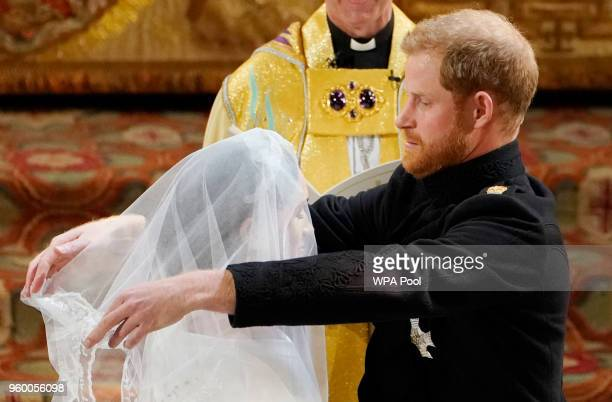 Prince Harry lifts the veil of Meghan Markle during their wedding ceremony in St George's Chapel at Windsor Castle on May 19 2018 in Windsor England