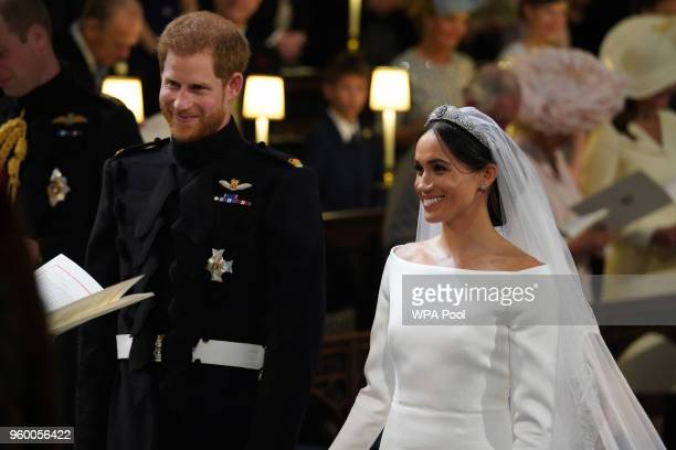 Prince Harry looks at his bride, Meghan Markle, as she arrived accompanied by Prince Charles, Prince of Wales during their wedding in St George's...