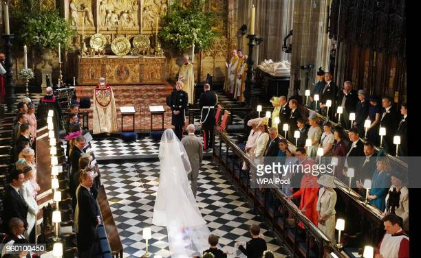 Prince Harry looks at his bride Meghan Markle as she arrived accompanied by Prince Charles Prince of Wales during their wedding in St George's Chapel...