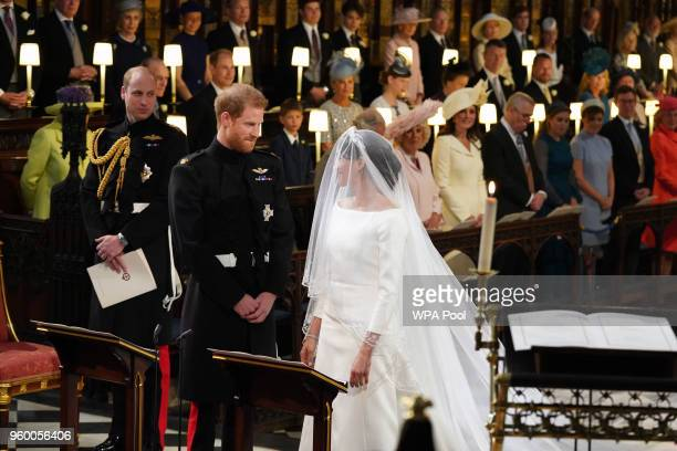 Prince Harry looks at his bride, Meghan Markle, as she arrives accompanied by Prince Charles, Prince of Wales during their wedding in St George's...