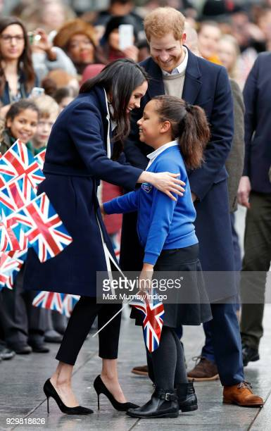 Prince Harry looks on as Meghan Markle hugs a young girl during a walkabout at Millennium Point before attending an event to celebrate International...