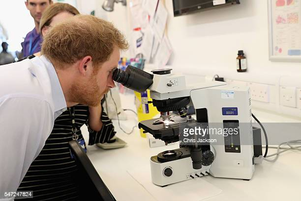 Prince Harry looks through a microscope at a sample of gonorrhoea as he visits Burrell Street Sexual Health Clinic on July 14 2016 in London England...