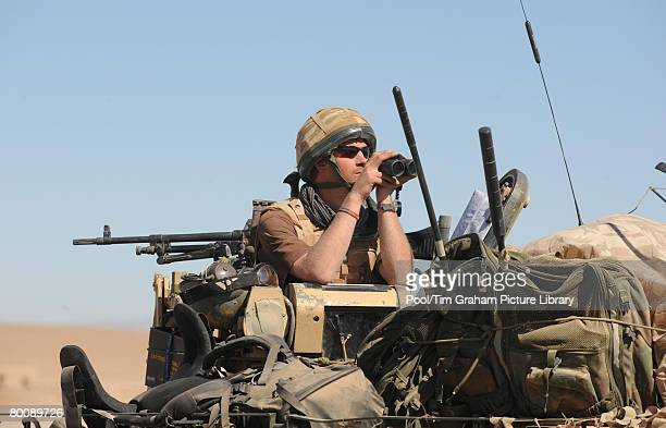 Prince Harry looks through binoculars from his position of the turret on his Spartan armoured vehicle in the desert of the Helmand province on...