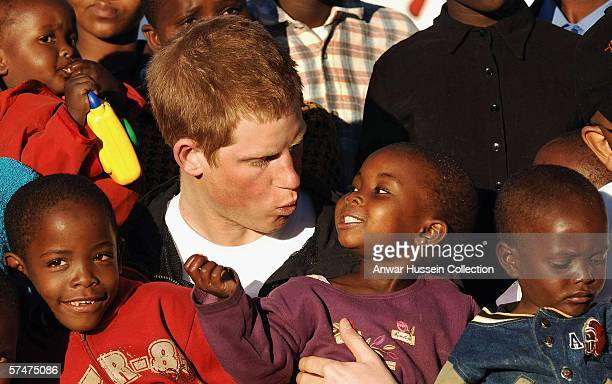 Prince Harry makes faces at children Mutsu and Lintle , in the grounds of the Mants'ase children's home while on a return visit to Lesotho on April...