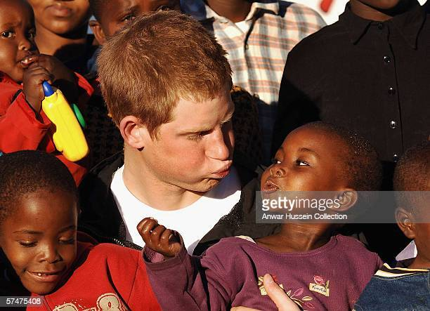 Prince Harry makes faces at Lintle in the grounds of the Mants'ase children's home while on a return visit to Lesotho on April 24 2006 in southern...