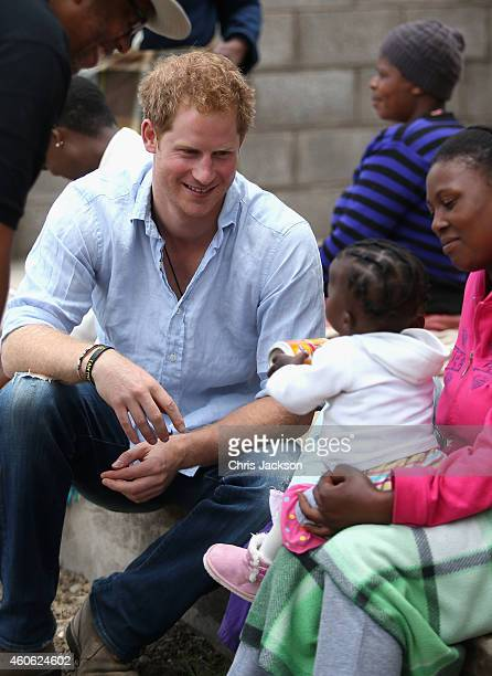 Prince Harry meets a baby during a visit to a herd boy night school constructed by Sentebale on December 8 2014 in Mokhotlong Lesotho Prince Harry...