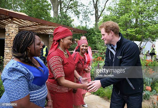 Prince Harry meets Basotho singers from Lesotho as he visits the Sentebale 'Hope In Vunerability' Garden during the annual Chelsea Flower show at...