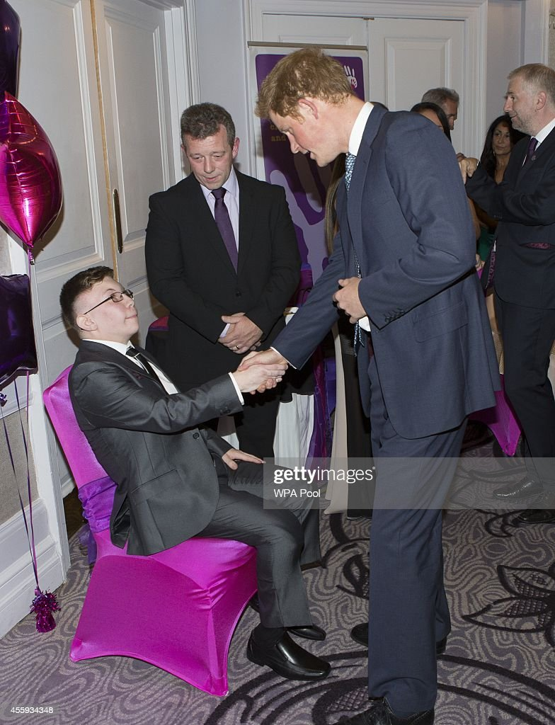 Prince Harry meets Calum Mayes (16), Inspirational young person 16-18 award winner with dad Russ during the WellChild awards at the London Hilton on September 22, 2014 in London, England.