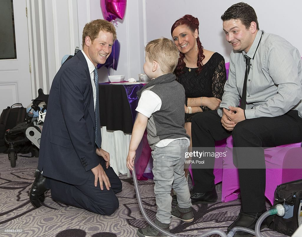 Prince Harry meets Carson Hartley (4) who suffers from lung disease, heart defect, Spina bifida and brittle bone disease, with his mum Kirsty and dad Damian, during the WellChild awards at the London Hilton on September 22, 2014 in London, England.