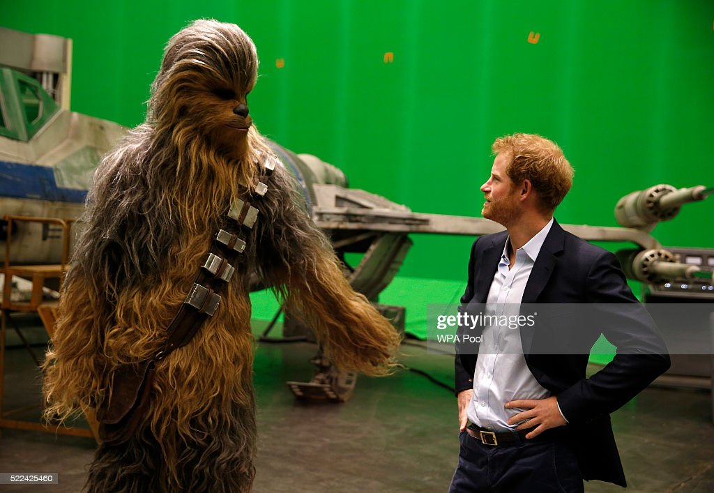 Prince Harry (R) meets Chewbacca during a tour of the Star Wars sets at Pinewood studios on April 19, 2016 in Iver Heath, England. Prince William and Prince Harry are touring Pinewood studios to visit the production workshops and meet the creative teams working behind the scenes on the Star Wars films.