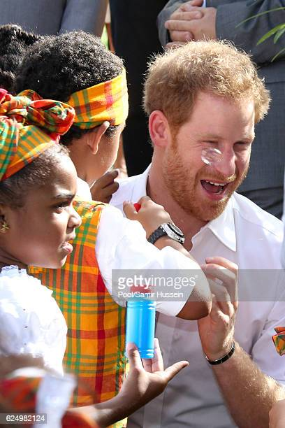 Prince Harry meets childen as he attends a Charities Showcase event in the tropical grounds of Government House on the second day of an official...