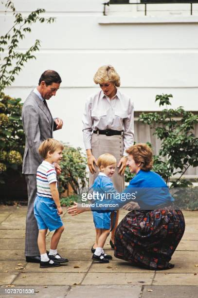 Prince Harry meets headmistress Jane Mynors on his first day at nursery school, watched by his parents Charles, Prince of Wales, and Diana, Princess...