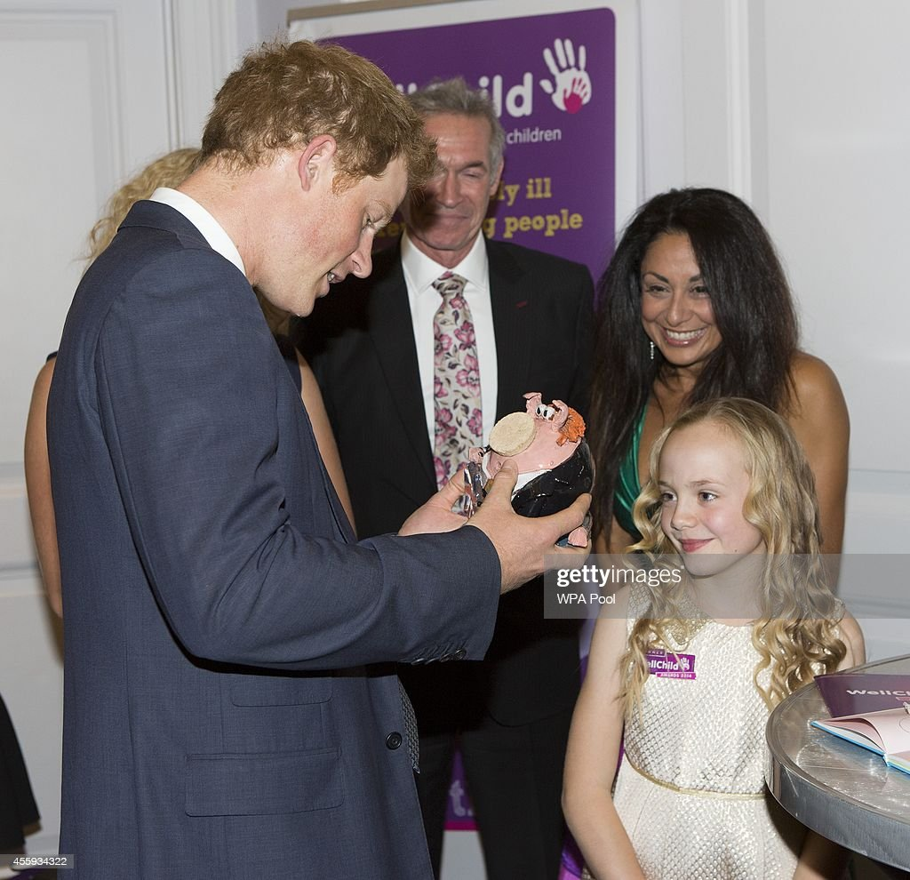 Prince Harry meets Olivia Ruston, good morning britain young hero award and presents Harry with a 'Harry look-a-like' piggy bank, during the WellChild awards at the London Hilton on September 22, 2014 in London, England.