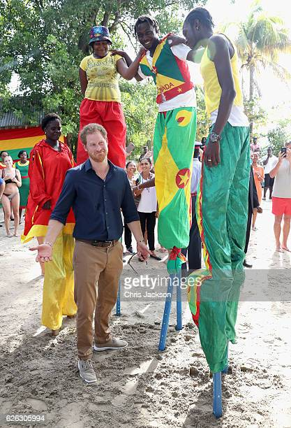Prince Harry meets stilt walkers on Grand Anse Beach as he visits Mangrove restoration projects ahead of visiting the coral reef on the ninth day of...