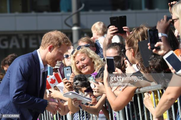 Prince Harry moves to pet a dog as he greets the crowds leaving The Centre for Addiction and Mental Health ahead of the Invictus Games 2017 on...