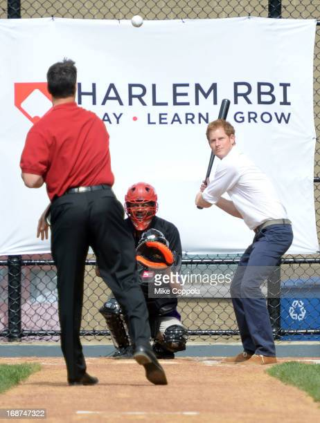 Prince Harry of Wales takes a pitch from professional baseball player Mark Teixeira during the fifth day of his visit to the United States at Harlem...