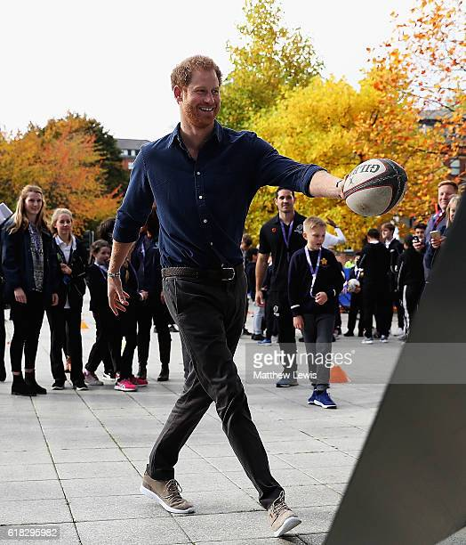 Prince Harry participates in a game of rugby with children from Chetwynd Primary Academy School during a visit to Coach Core at The National Ice...
