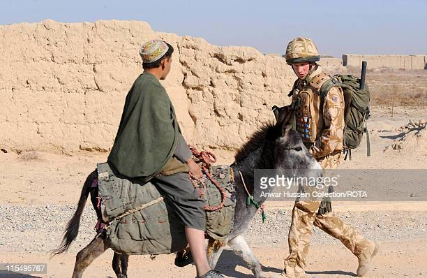 Prince Harry passes a local on a donkey as he patrols the deserted town of Garmisir on January 2, 2008 in Helmand Province, Afghanistan.
