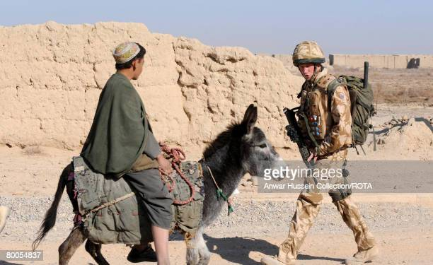 Prince Harry passes a local riding a donkey as he patrols through the deserted town of Garmisir on January 2 2008 in Helmand Province Afghanistan