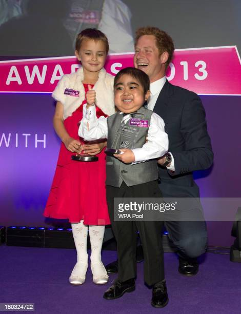 Prince Harry Patron of WellChild poses on stage with award winners Madison Kirk age 6 and Jonathan He age 6 from Milton Keynes during the 8th annual...