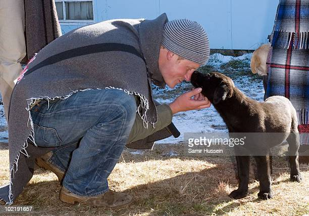 Prince Harry pets a puppy during a visit to the Semongkong Children's Centre on June 17 2010 in Semongkong Lesotho The Princes are on a joint trip to...