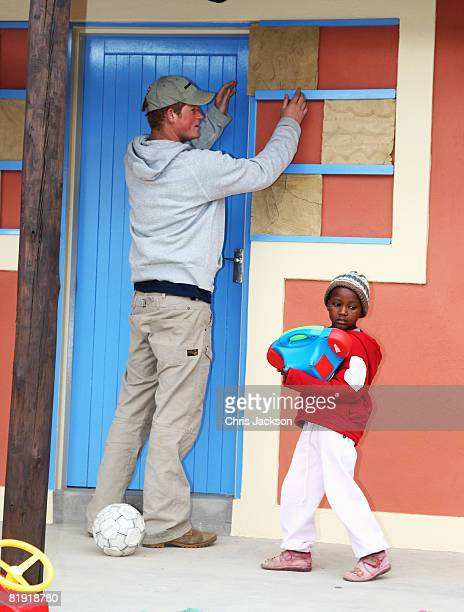 Prince Harry places a special tile he designed during a visit to LCCU on July 9, 2008 in Maseru, Lesotho. Prince Harry and 26 soldiers from the...