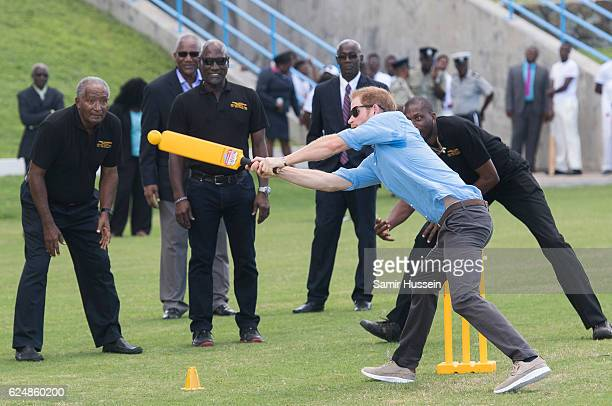 Prince Harry plays cricket as Sir Andy Roberts Sir Vivian Richards and Sir Curtly Ambrose look on during a Youth Sports Festival at the Sir Vivian...