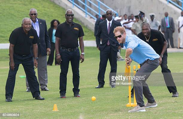 Prince Harry plays cricket as Sir Andy Roberts, Sir Vivian Richards and Sir Curtly Ambrose look on during a Youth Sports Festival at the Sir Vivian...