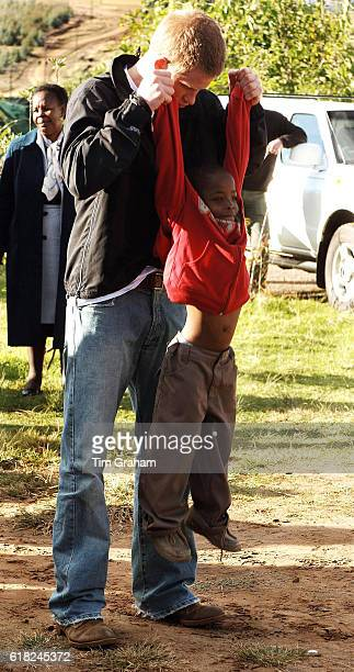 APRIL 28 2006*** Prince Harry plays games with his old friend Mutsu Potsane in the grounds of the Mants'ase children's home while on a return visit...