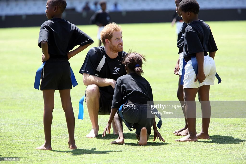 Prince Harry plays tag rugby with a group of children on December 1, 2015 at the Kings Park Stadium in Durban, South Africa. The British Royal also met with young surfers of Surfers Not Street Children.
