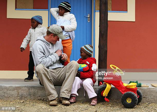Prince Harry plays with Molise, aged four, during a visit to LCCU on July 9, 2008 in Maseru, Lesotho. Prince Harry and 26 soldiers from the Household...