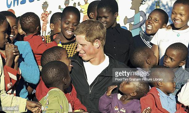 Prince Harry plays with Mutsu Potsane and other children in the grounds of the Mants'ase children's home during a return visit to Lesotho in southern...