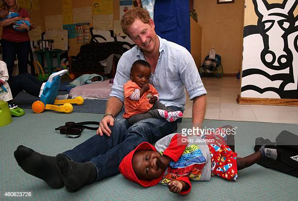 Prince Harry plays with two young children during a visit to the organisation supported by Sentebale 'Touching Tiny Lives' on December 8 2014 in...