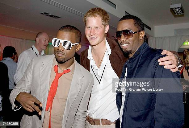 Prince Harry poses for a photograph with P Diddy and Kanye West at the after concert party the Princes hosted to thank all who took part in the...