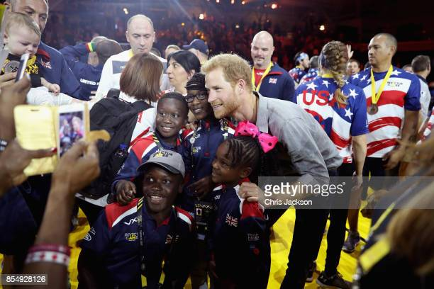 Prince Harry poses for a photograph with the UK Armed Forces Team Georgian Team and USA Team after the Sitting Volleyball Finals during the Invictus...