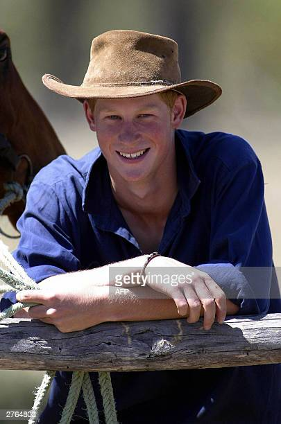 Prince Harry poses next to his horse 'Guardsman' with the team mustering herd bulls at the Tooloombilla cattle farm in Queensland 27 November 2003...