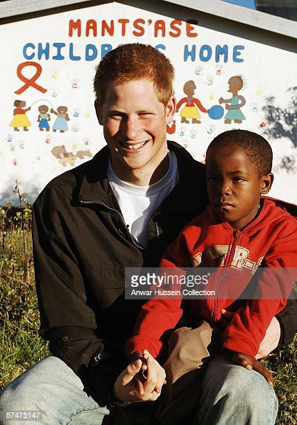 Prince Harry poses with an old friend, Mutsu Potsane, in the grounds of the Mants'ase children's home while on a return visit to Lesotho on April 24,...