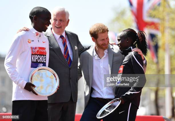 Prince Harry poses with Eliud Kipchoge of Kenya and Vivian Cheruiyot of Kenya as they receive their trophies following their first place results...