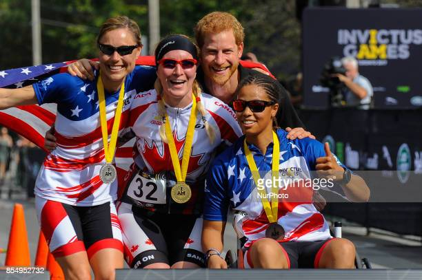 Prince Harry poses with medalists in the Women's Recumbent Bike IRECB1 time trial, silver medalist Amy Dotson of the United States, gold medalist...