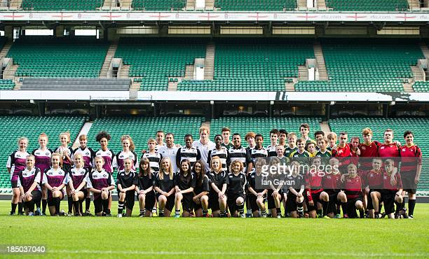 Prince Harry poses with the teams on the pitch during the RFU All School programme coaching event at Twickenham Stadium on October 17, 2013 in...