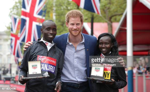 Prince Harry poses with the winner of the Men's Elite race Kenya's Daniel Wanjiru and the winner of the Women's race Kenya's Mary Keitany during the...