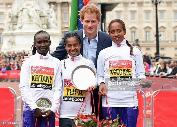 Prince Harry poses with Tigist Tufa winner of the Womens Elite race 2nd place Mary Keitany and 3rd place Tirfi Tsegaye during the London Marathon on...
