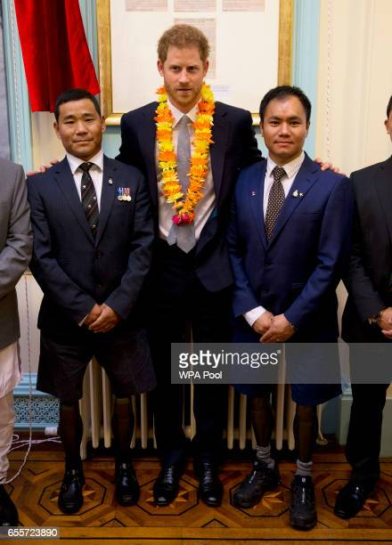 Prince Harry poses with two Gurkhas who he served with in Afghanistan Rifleman Vinod Budhathoki and Corporal Hair Budha Magar as he attends a...