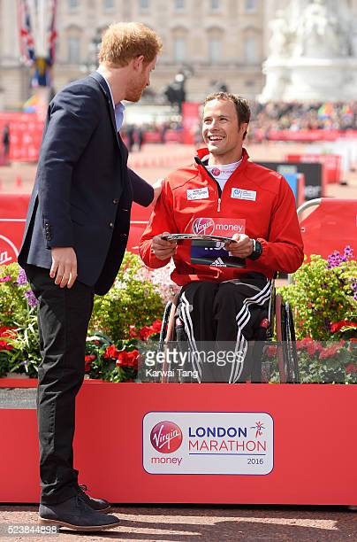 Prince Harry presents the trophy to the mens wheelchair winner Marcel Hug at the Virgin London Marathon 2016 on April 24 2016 in London England