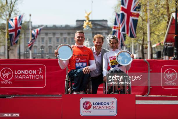 Prince Harry Prince of Wales poses with David Weir of Great Britain and Madison de Rozario of Australia as they receive their trophies following...