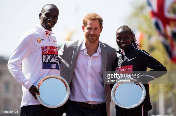 Prince Harry Prince of Wales poses with Eliud Kipchoge of Kenya and Vivian Cheruiyot of Kenya as they receive their trophies following their first...