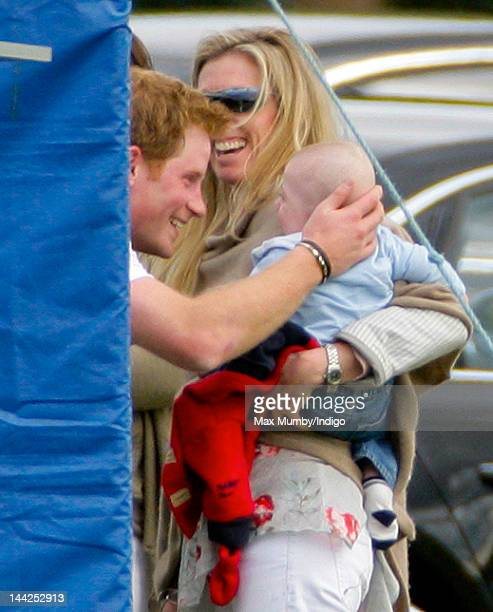 Prince Harry pulls faces at and strokes a baby after playing in the Audi Polo Challenge charity polo match at Coworth Park Polo Club on May 12 2012...