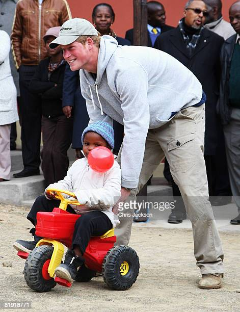 Prince Harry pushes Mojabeng , aged four, on a toy tractor during a visit to LCCU on July 9, 2008 in Maseru, Lesotho. Prince Harry and 26 soldiers...