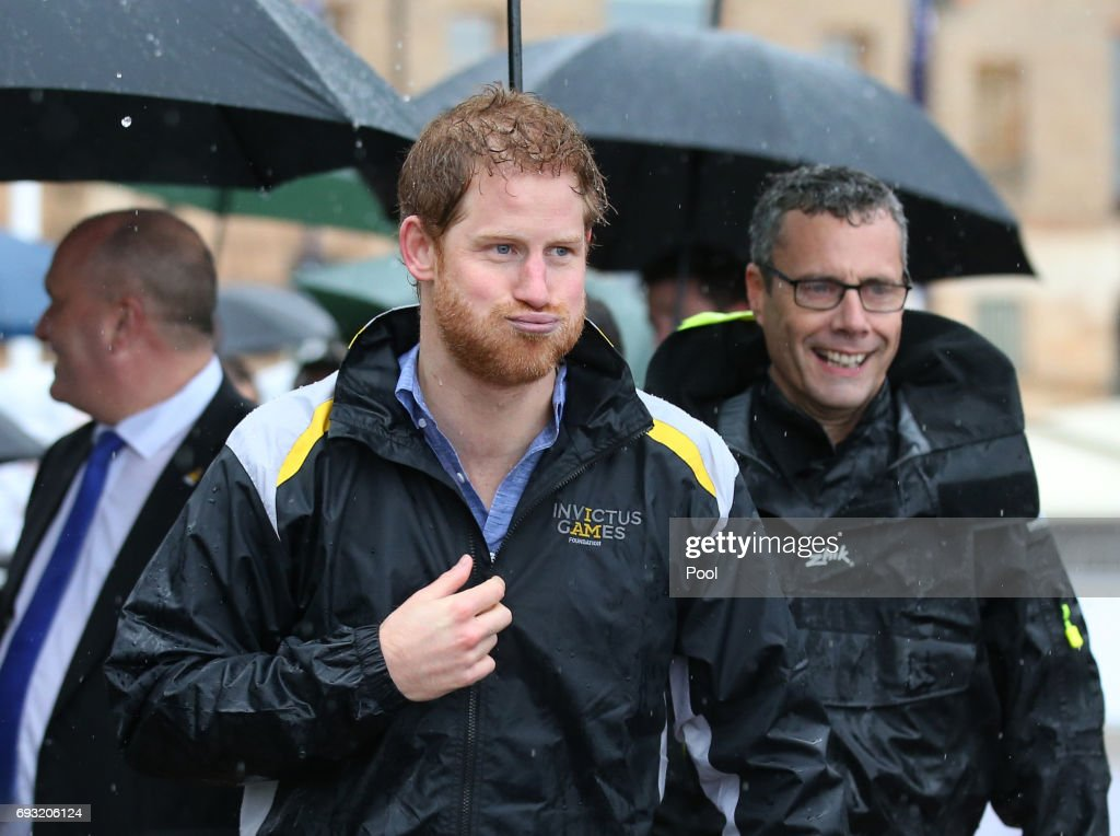 Prince Harry reacts as he walks away after meeting members of the public in the pouring rain at The Rocks on June 7, 2017 in Sydney, Australia. Prince Harry is on a two-day visit to Sydney for the launch of the Invictus Games Sydney 2018. The fourth Invictus Games will be held in Sydney from 20th to 27th October, 2018 and will include over 500 competitors from 17 nations competing in 10 adaptive sports events.